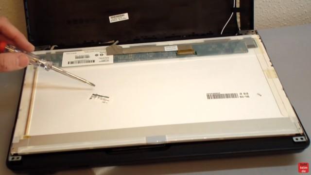 Notebook Display Reparatur - defektes Display ausbauen und tauschen - hinten sind auf dem Display verschiedene Aufkleber